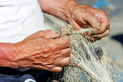 Fisherman cleans his fishing nets